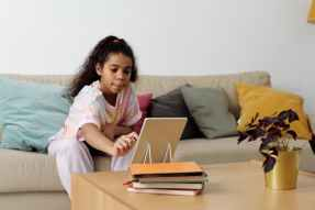 girl sitting on sofa while using tablet computer